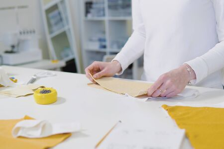 Fashion designer or tailoress cutting fabric while working with drawing sketch, material at worktable. Garment business concept. view from the top