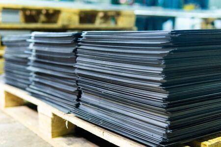 Blachy stalowe składowane w stosach w paczkach w magazynie wyrobów metalowych. Blacha zwietrzała dla budownictwa. Korozja metalu