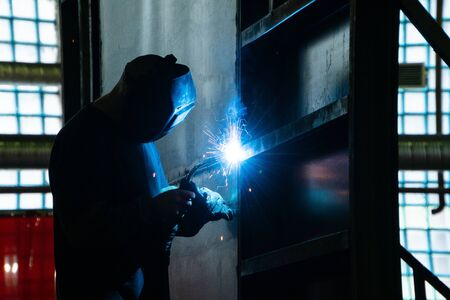 Welder in his workshop welding metal, lots of sparks flying around