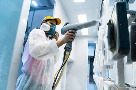 Powder coating of metal parts. A woman in a protective suit sprays white powder paint from a gun on metal products