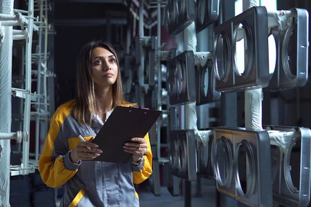 A young pretty white woman works in the paint shop of the plant, she checks the unpainted metall products and making record in check list. Reklamní fotografie