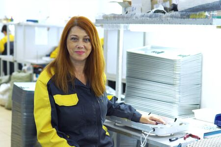 Portrait of red-haired woman factory worker sitting near production Assembly line at the plant for production of electrical products Reklamní fotografie