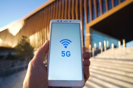 man hand holding a smartphone and 5g signal symbol on screen with broadcast antenna icon on city background. High speed mobile web connection technology concept 版權商用圖片