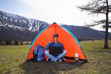 young man with a laptop sitting in a tent against the mountains and hills of Altai and talking on a cell phone. The concept of remote work or freelancer lifestyle