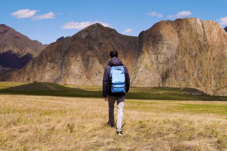 tourist in a cap and jacket with a backpack goes on the grass in the direction of mountains. Exploring, researches and expedition concept