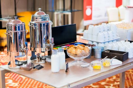 Coffee, bottles of milk, cups on catering table at conference. Group of empty white ceramic cups for coffee or tea in outside buffet at the business meeting event or hotel. 스톡 콘텐츠