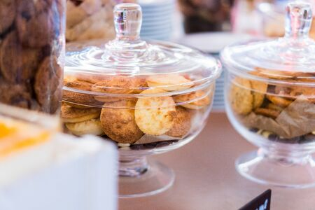 Shortbread cookies in glassware and other sweets on the buffet table during the coffee break.