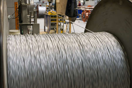 A coil of power electric cable in yellow insulation on a metal coil