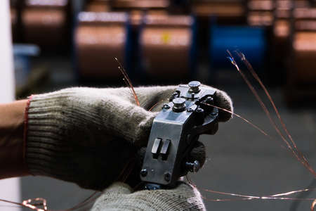 gloved hands connect the copper cable to the core with a special tool