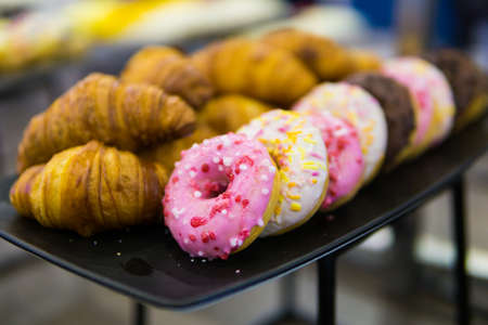 croissants, donut and other sweets on the buffet table during the coffee break