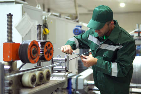 factory worker in a robe and cap checks the performance of the device for the production of cable products from a copper core Reklamní fotografie