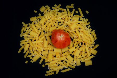Tomato surrounded by Italian pasta