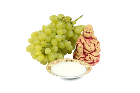 fascicule: Still life of statues of the Buddha, the saucer of milk and bunch of grapes. Isolation on a white background.