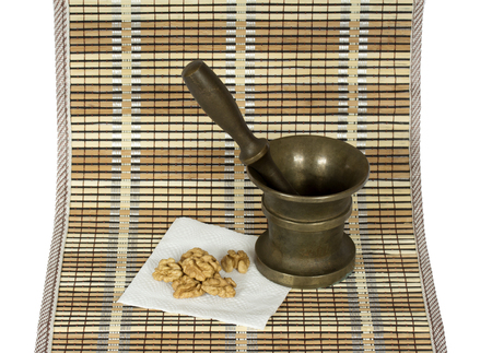 pounder: Walnut and the copper pounder (mortar) on the  matting. On white Stock Photo