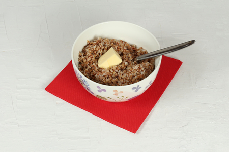 buckwheat: Buckwheat porridge with butter. In a bowl on a red napkin. Clipping path