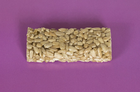 brittle: Seed brittle (sunflower brittle) on a purple background. Stock Photo