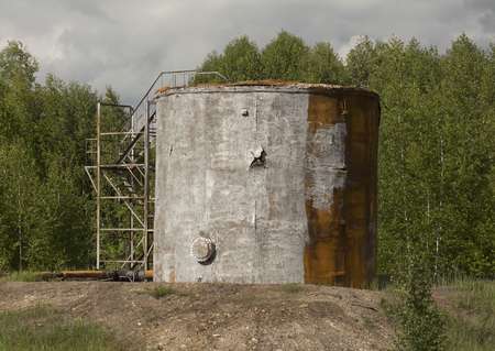 storage tank: Old oil storage tank on the forest background.