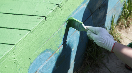 colouration: The painter paints the wooden structure in the green color