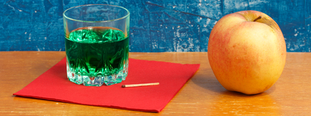 ajenjo: Absinthe, match and apple. Still life on a contrasting yellow-blue background.