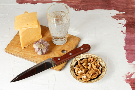indigence: Grunge food. Still life with cheese, garlic, walnuts and mineral water.