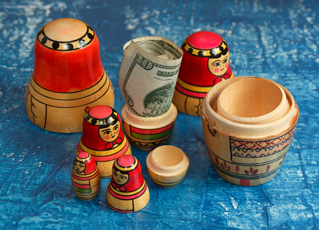 matriosca: Group nesting dolls and ten dollars on a blue background Stock Photo