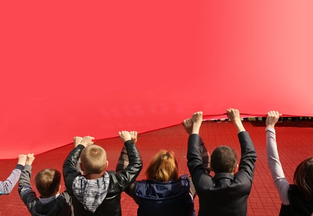 socialist: Background. Children hold cloth of red flag