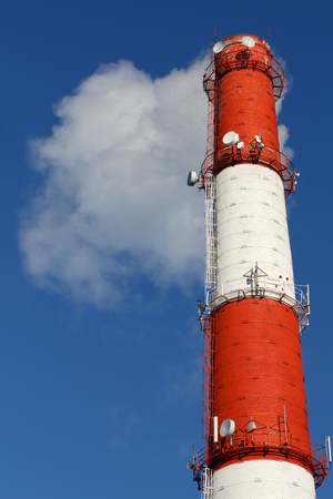 deleterious: Industrial chimney and smoke in the background of blue sky Stock Photo