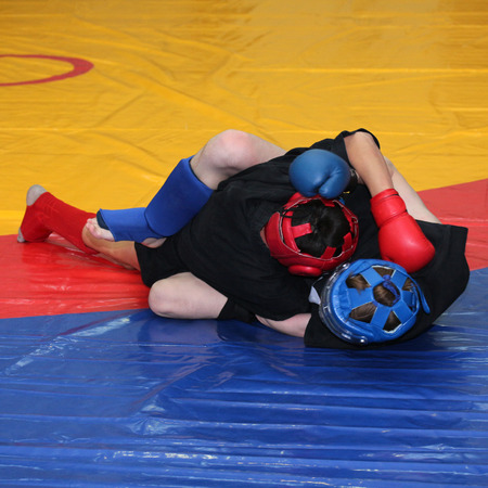 folkstyle: Two young fighters in sports protection on the wrestling mat cover
