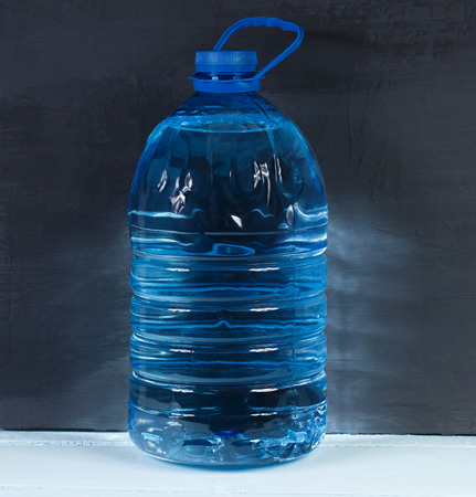 litre: 5 liters. Big plastic bottle of potable water, barrel with handle on a dark background