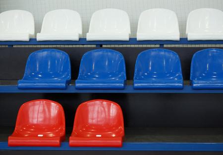 Gym seats. Empty plastic chairs in stadium