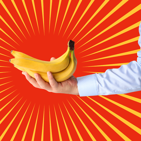 Bunch of bananas  in hand on stylized background of sun. Pop art illustration