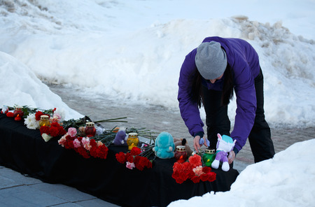 Winter, snow. The girl puts the toy to the mourning memorial