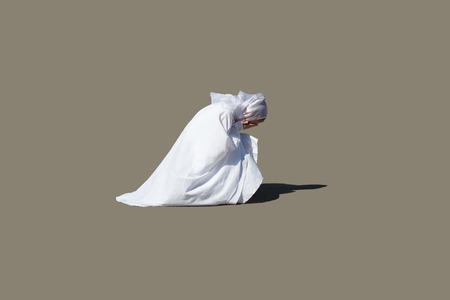 A beautiful woman in white kneeling in prayer, her eyes closed, head bowed and hands clasped.