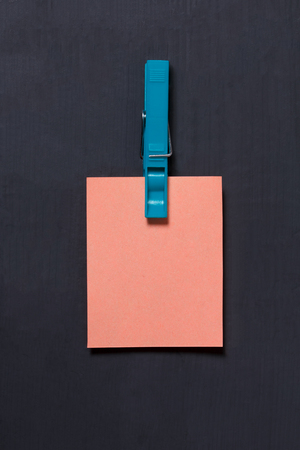 Empty pink mockup paper sticker hanging with a clothespin on dark background. Space for your text