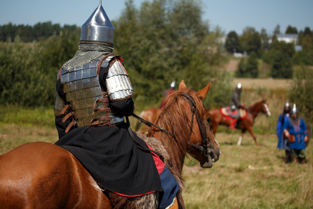 Reconstruction. Medieval armored knight on horse. Equestrian soldier in historical costume. Reenactor is in the summer field