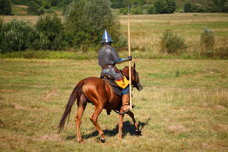 Reconstruction. Medieval armored knight whith lance on horse. Equestrian soldier in historical costume. Reenactor is in the summer field