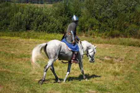 Reconstruction. Medieval armored knight on white horse from fantasy. Equestrian soldier in historical costume. Reenactor is in the summer field Stock Photo