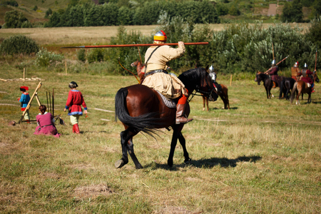 Reconstruction. Country. Medieval knight whith lance on horse from fantasy. Equestrian soldier in historical costume. Reenactor is in the summer field