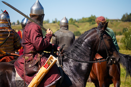 Reconstruction. Medieval armored knight on horse. Equestrian soldier with saber in historical costume. Reenactor is in the summer field