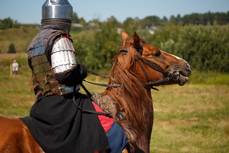 Reconstruction. Medieval armored knight on horse from fantasy. Equestrian soldier in historical costume. Reenactor is in the summer field Stock Photo