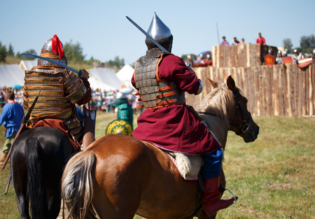 Reconstruction. Country. Medieval knight whith lance on horse from fantasy. Equestrian soldier in historical costume. Reenactor is in the military camp