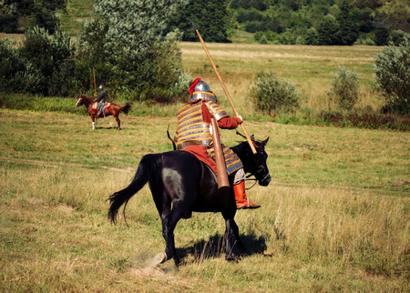 Two knights fight. Medieval armored equestrian soldiers with lances. Riders on  horses are in the summer field