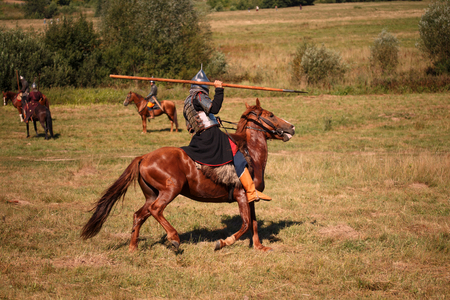 Reconstruction. Medieval armored knight with lance on horse from fantasy. Equestrian soldier in historical costume. Reenactor is in the summer field