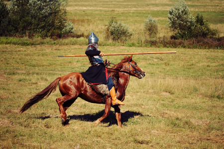The knight fight. Medieval armored equestrian soldier with lance. Rider on  horses are in the summer field Stock Photo