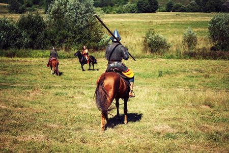 Summer field. Medieval armored knight with lance on horse from fantasy. Equestrian soldier in historical costume