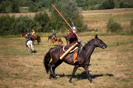 Reconstruction. Medieval armored knight with lance on horse from fantasy. Equestrian soldier in historical costume. Rider is in the summer field