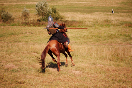 Medieval armored knight with lance on horse catching up with the fleeing woman and her children. Equestrian soldier in historical costume in the summer field Stock Photo