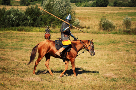 Medieval armored equestrian soldiers with lances on horses. Riders are in the summer field
