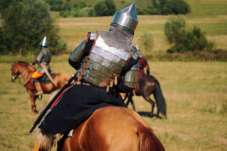 Knight on horse. Medieval armored equestrian soldiers. Riders are in the summer field