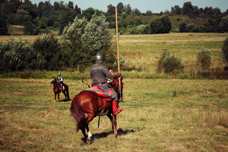 Knight tournament. Medieval armored equestrian soldiers with lances on horses. Riders are in the summer field Stock Photo